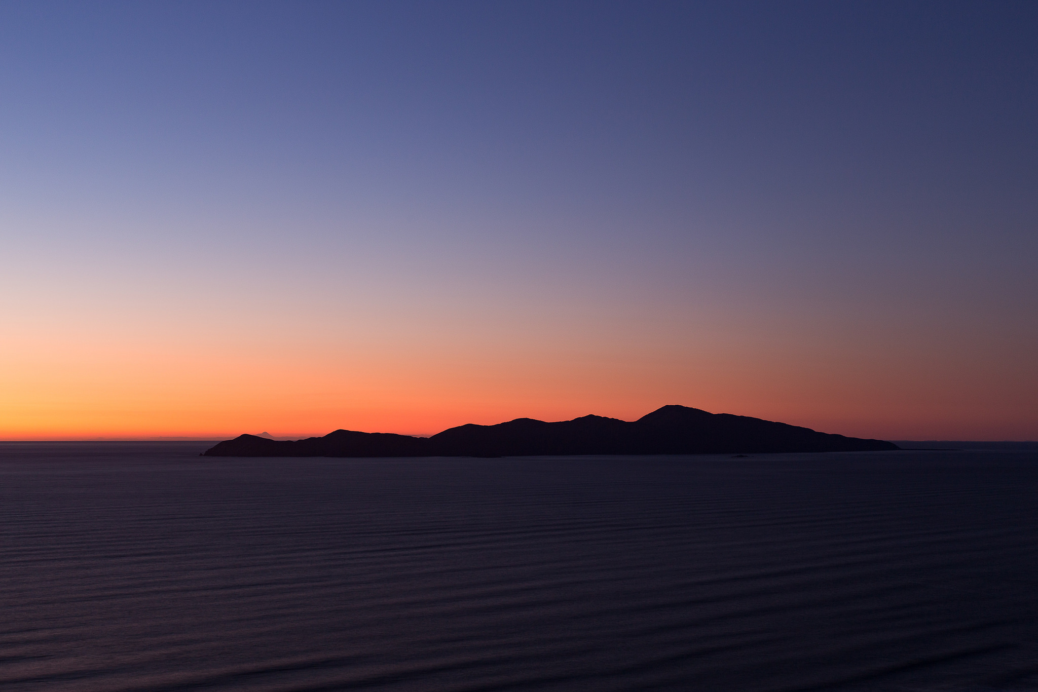 Kapiti Island silhouette with Mount Taranaki peeking over the southern end (left hand side)