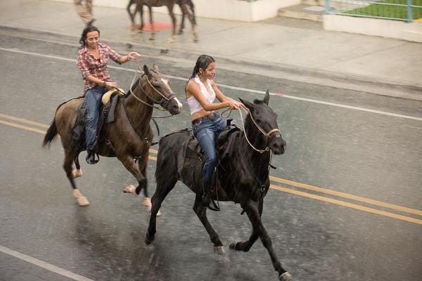 Riders gallop down the street through the rain.